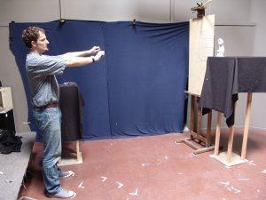 """A festő a """"látványméretű rajzot"""" gyakorolja és éppen egy mérést végez."""