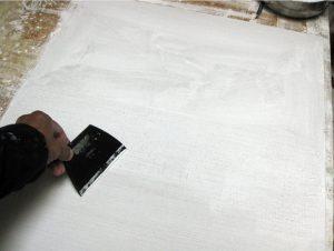 Egy életlen késsel, spaklival, vagy akár egy vonalzóval, lehúzzuk a felesleges anyagot a felületről, ha vásznat alapozunk, akkor közben passzírozzuk is a vászon szemek közé az anyagot. Ugyanúgy, ahogy az enyvezésnél leírtuk.